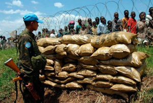 An Indian UN peacekeeper stands guard as displaced civilians seek shelter near the UN base in Kiwanja, eastern DRC, 2006. (from the cover photo of Peaceland, ©David Lewis/Reuters/Corbis)