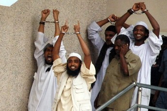 Four Sudanese convicts raise their handcuffs as they are escorted out of the courtroom in the capital Khartoum, 24 June 2009. (REUTERS/Mohamed Nureldin Abdallah)