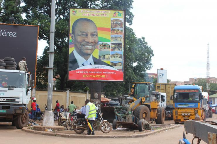 People pass in front of an electoral campaign poster for incumbent President Alpha Conde in Conakry, Guinea, Sept. 10, 2015. Saliou Samb/Reuters