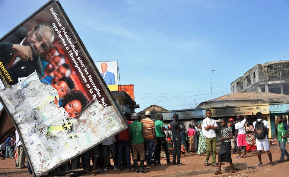 People gather around a destroyed commercial building on October 10, 2015 in Conakry, after clashes between rival political parties ahead of Guinea's presidential election on October 11, 2015 (AFP Photo/Cellou Binani)