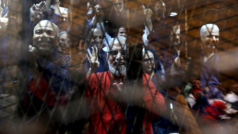 Muslim Brotherhood's General Guide Mohamed Badie (C) waves with the Rabaa sign, symbolizing support for the Muslim Brotherhood, with other brotherhood members at a court on the outskirts of Cairo, Egypt in this May 16, 2015 file photo. (Reuters)