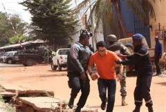 In this Friday, Nov. 20, 2015 file photo, Mali troopers assist a hostage to leave the Radisson Blu hotel to safety after gunmen attacked the hotel, in Bamako, Mali. The al-Qaida-claimed attack on a Mali hotel may have been partly aimed at asserting the global terror network's relevance as it faces an unprecedented challenge from the Islamic State group for leadership of the global jihadi movement. While the two groups share similar goals they have been bitterly divided over strategy and leadership, and have come to blows in Syria. HAROUNA TRAORE/AP