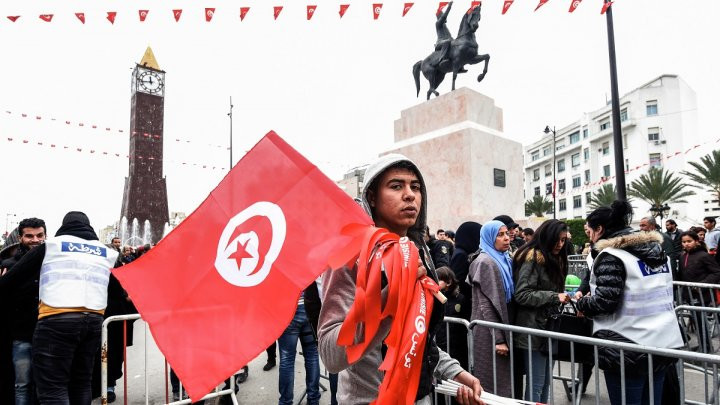 © Fethi Beaid, AFP| A Tunisian peddlar selling national flag crosses a police roadblock on his way to a rally on January 14, 2017 in the capital Tunis marking the sixth anniversary of the 2011 revolution.