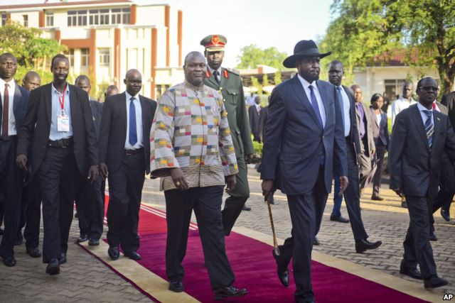 FILE - South Sudan's rebel leader and now Vice President Riek Machar, center-left, walks with President Salva Kiir, center-right, after being sworn in at the presidential palace in the capital Juba, South Sudan, April 26, 2016.