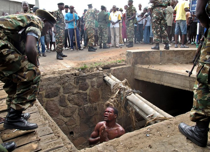 7 May 2015: A man begs for help from the military as he stands in a drain where he had hid to escape a lynch mob at the Cibitoke district of the Burundi capital, BujumburaAymeric Vincenot/AFP