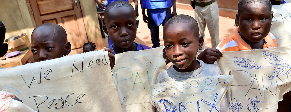 Children holding peace signs wait to greet Pope Francis during his visit to a refugee camp. Bangui, Central African Republic, November 29, 2015. (Giuseppe Cacace/AFP/Getty Images)