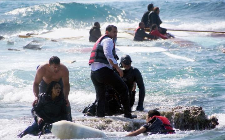 A man rescues an migrant from the Aegean sea CREDIT: AP