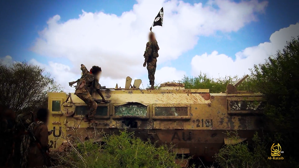 The flag of al Qaeda waves over a destroyed African Union armored personnel carrier