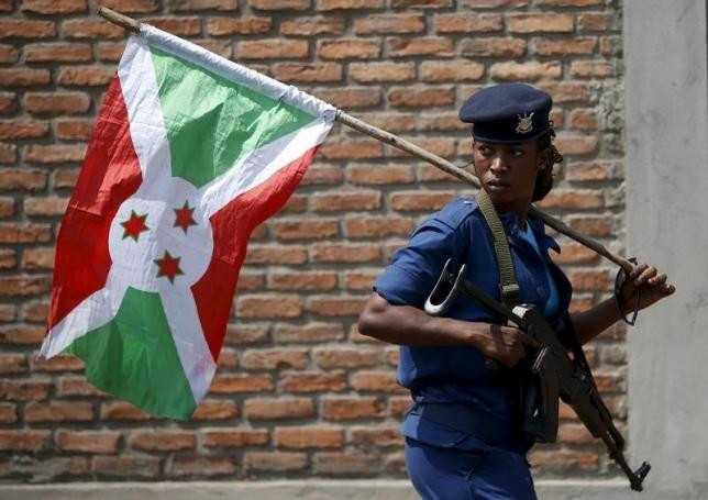 A policewoman carries a Burundi flag during a protest against President Pierre Nkurunziza's decision to run for a third term in Bujumbura, Burundi, May 29, 2015. REUTERS/GORAN TOMASEVIC