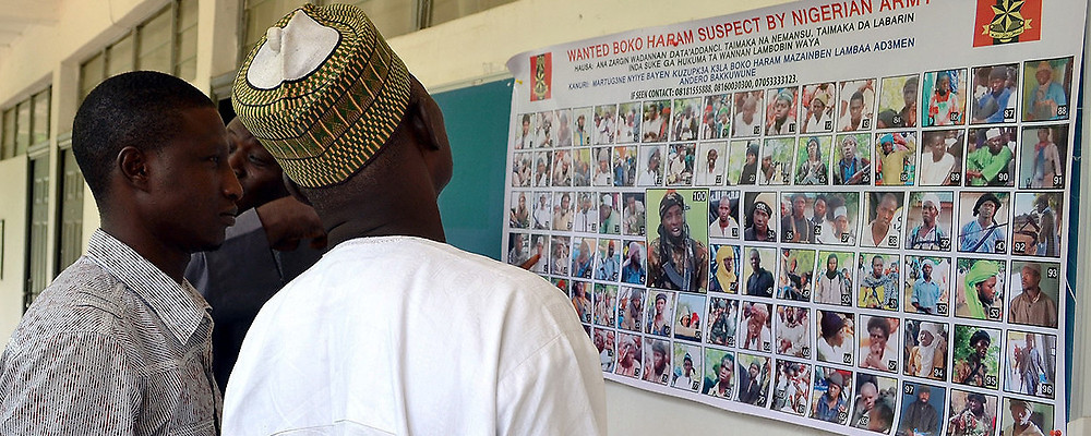 Locals study a poster featuring Boko Haram members wanted by the Nigerian army. Maiduguri, Nigeria, October 28, 2015 (AFP/Getty Images)