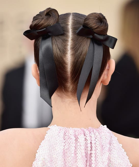 Black ribbon hair bows in space buns on Millie Bobby Brown.