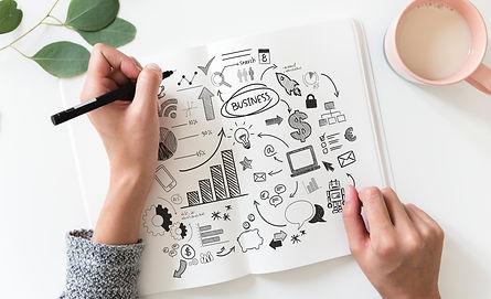Дланки кои држат скица на која пишува бизнис и други симболи