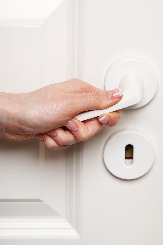 Close up of Female hand on door handle.j