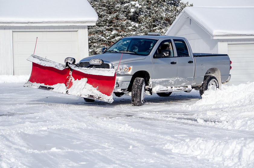 silver truck moving snow on a winter's d