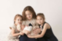 Portrait of a newborn baby girl with her siblings on a white backdrop during a cny newborn photography portrait session