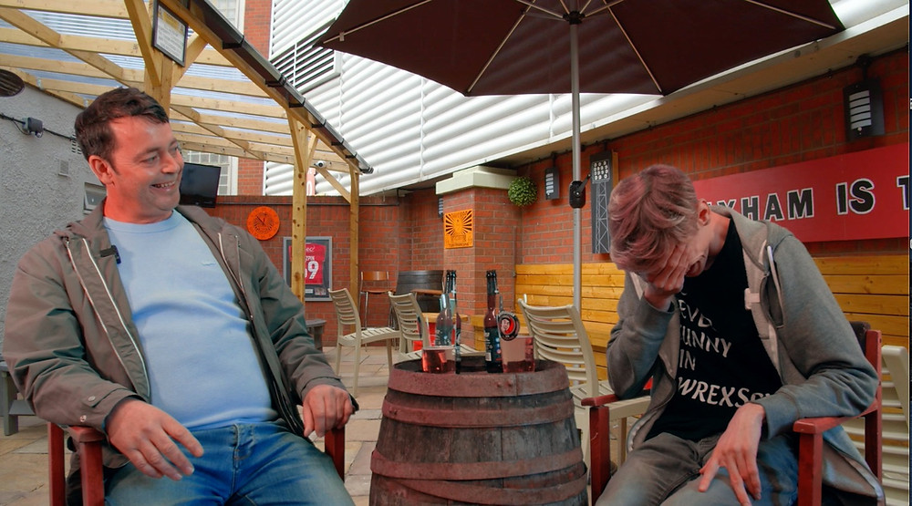 2 men sitting in a beer garden outside Wrexham FC