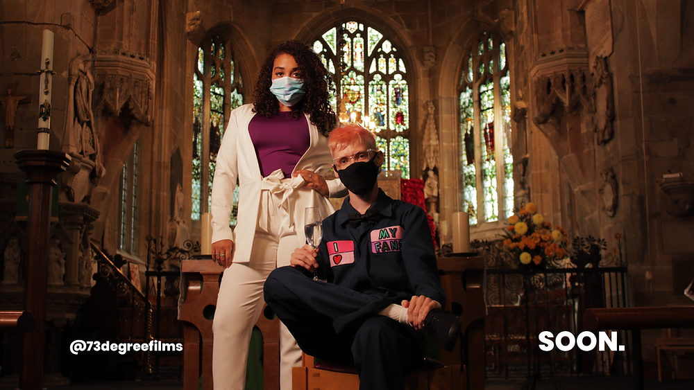 2 young people pose in front of a church altar while wearing face masks.