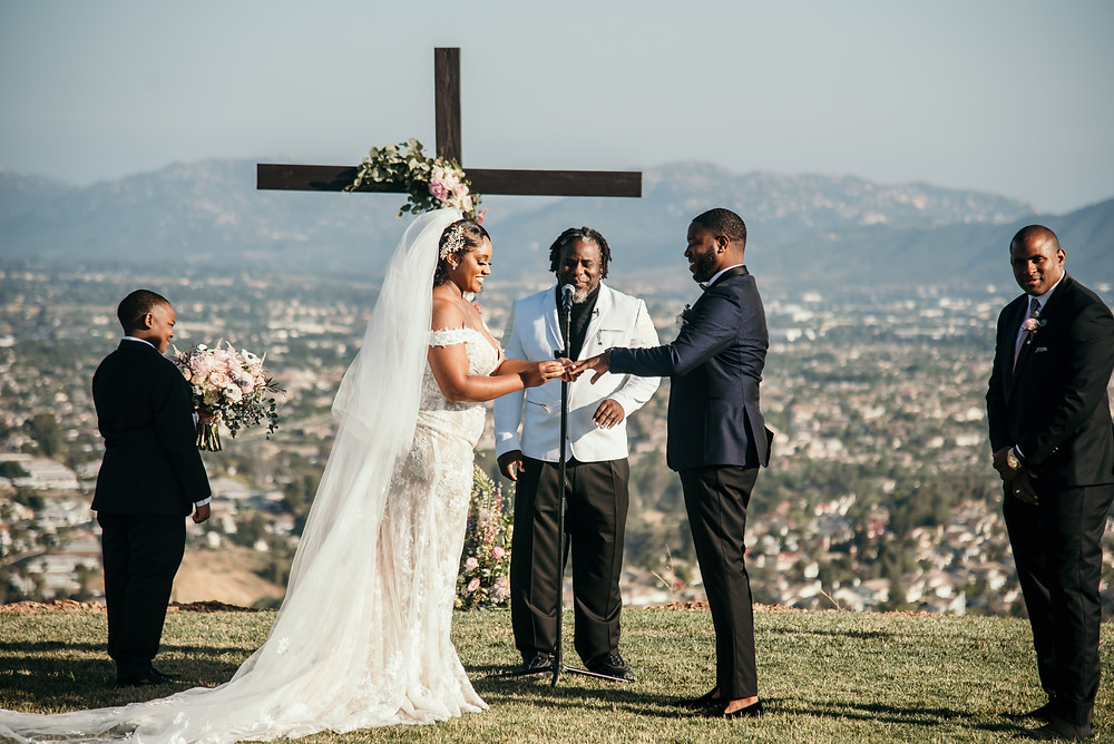 Bride and groom in front of cross at Christian wedding by Joy Photo and Video.