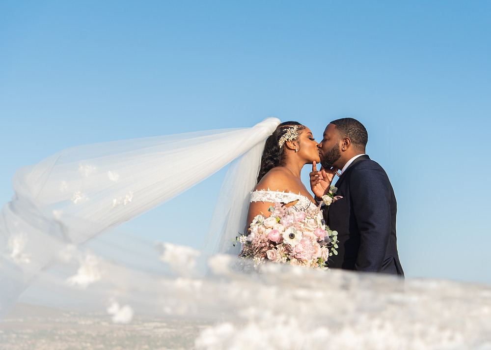 Christian couple kissing with bridal veil in Dallas, Texas.
