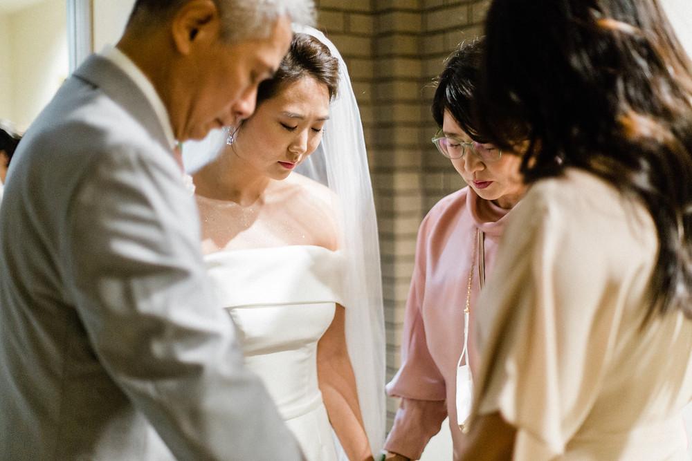 Christian bride praying with family in Dallas, Texas religious wedding.