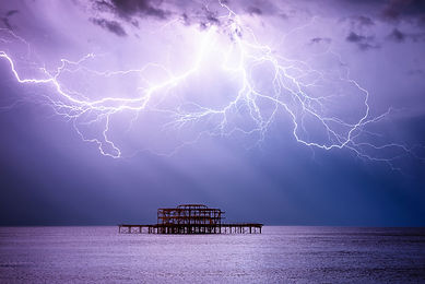 Brighton West Pier at night lit by a huge thunder