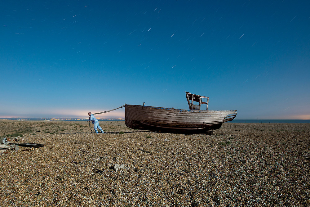 A man in pyjamas towing a boat on the beach