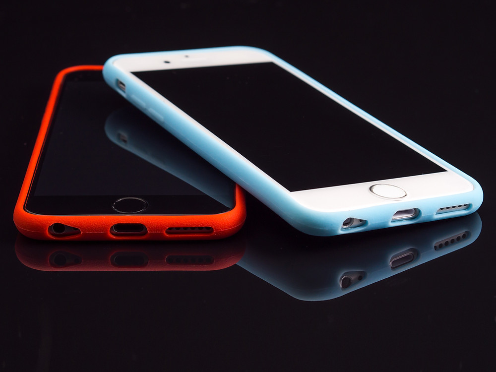 Two iPhone 6 smartphones laying on a black table