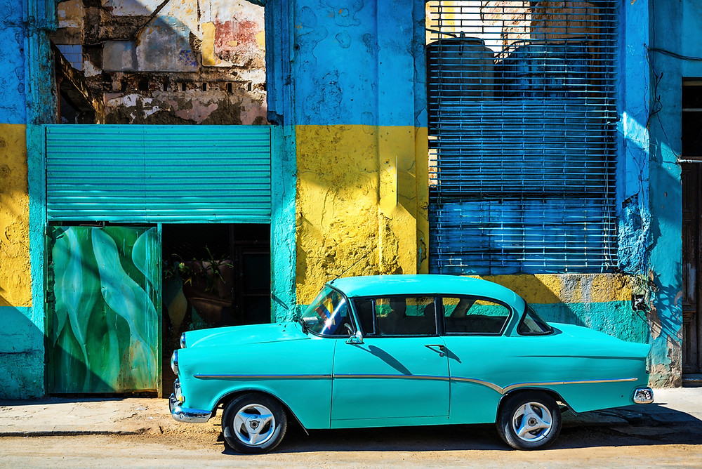 Teal car from the 1950s in front of a yellow, blue and teal industrial building in Havana, Cuba.