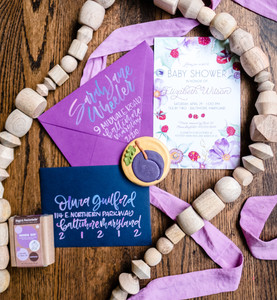 flat lay baby shower garland sugar cookies purple navy plum pink invitation hand written script