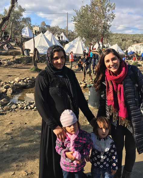 Alex helps Nadia and her two daughters pick out new clothes in Camp Moria