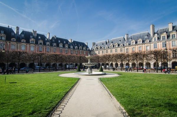 Photo de la Place des Vosges et sa fontaine centrale. Le Marais