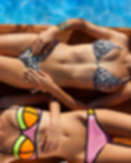 Two young women wearing bikini lying dow
