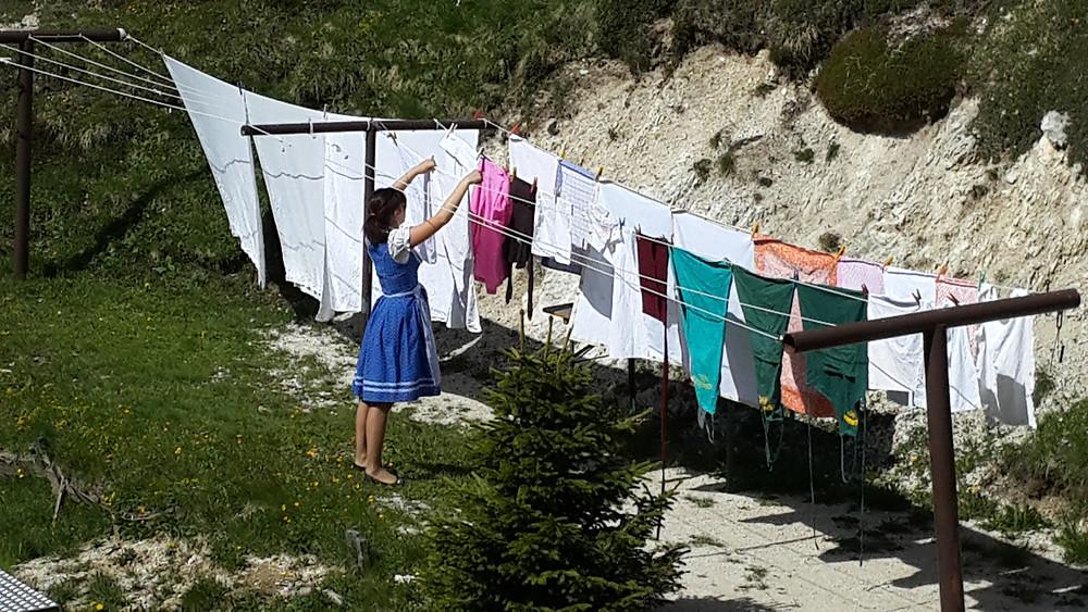אישה תולה כביסה בדולומיטים