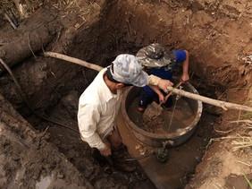 Les ouvriers creusent la source d'eau au bord de la rivière Beng et construisent le puit.