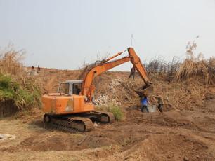 La pelleteuse creuse la source d'eau. Il y a du bois sous la terre.