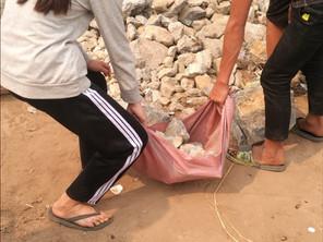 Les élèves du collège de Navang portent des pierres à la source pour la filtration d'eau.