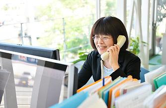 セゾンハウス女性社員が笑顔で電話対応中の様子