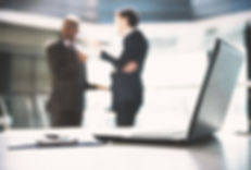 Businessmen talking in front of a laptop computer