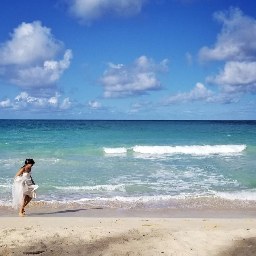 Bride running in the water in Hawaii