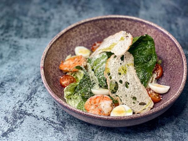 Цезарь с креветками, томатами Черри, лисстьями романо, сыром Пармезан и соусом из анчоусов