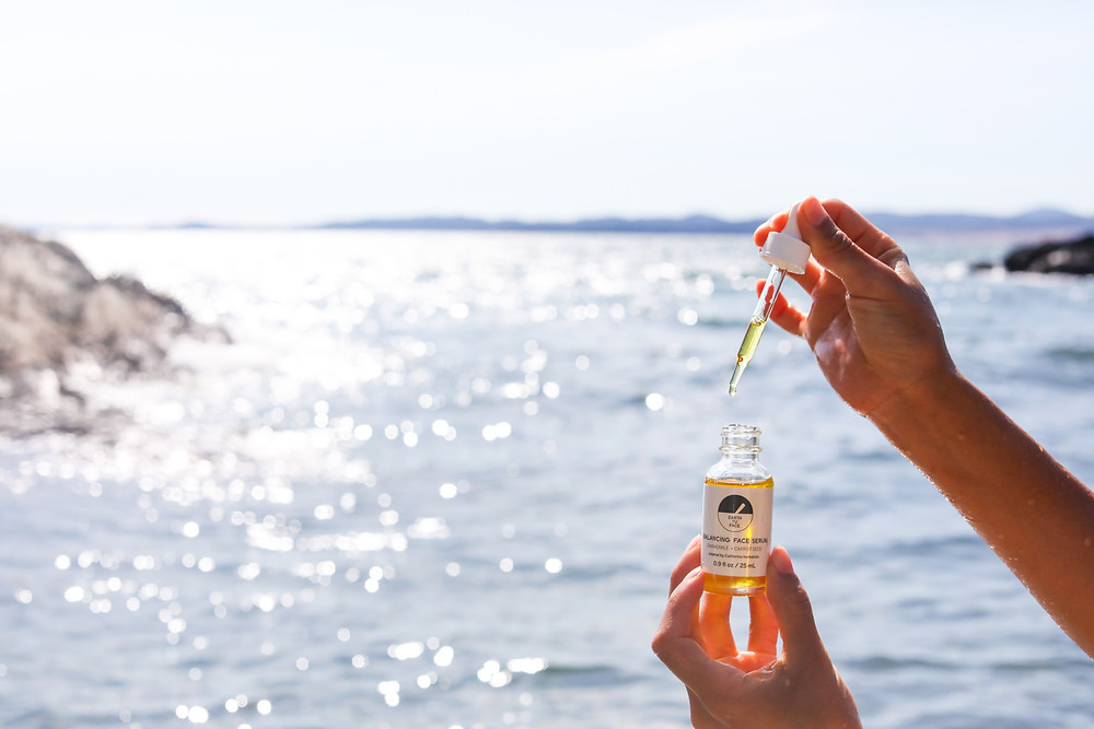 Earth Tu Face Serum bottle with dropper being held in the air overlooking the ocean