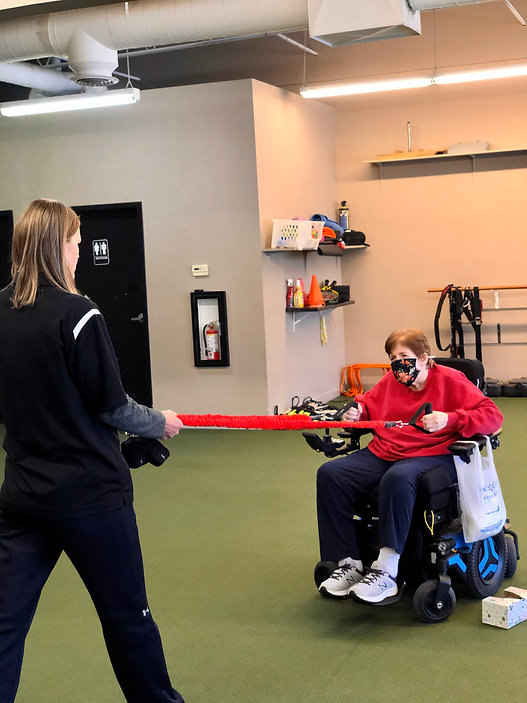 Woman on wheelchair pulls on elastic band with help of trainer.
