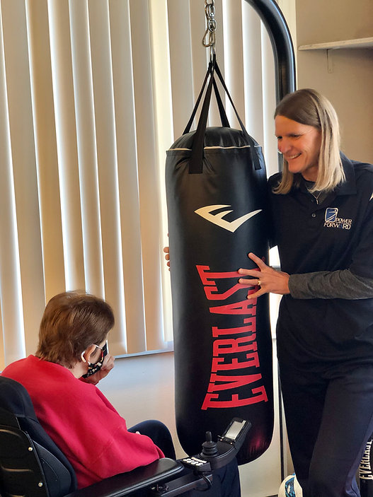 woman on wheelchair in front of punching bag being held by a trainer.
