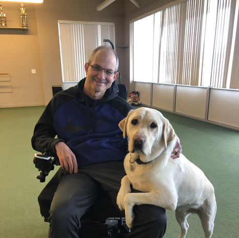Daryl, MSforward's founder, sitting in his chair next to their dog, Vander.