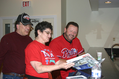 Tommy looking at Phillies book w couple.