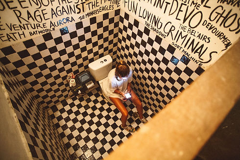 woman-sitting-on-toilet-bowl-with-smartp