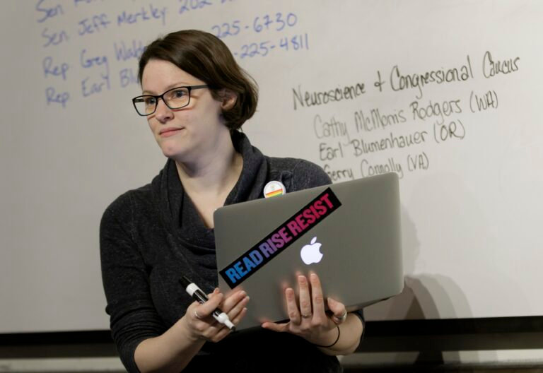 OHSU student Mollie Marr pictured in front of a whiteboard with a MacBook in hand