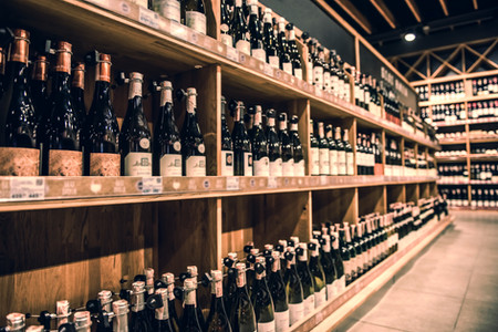 Wine bottles lined up on a shelf in a store.