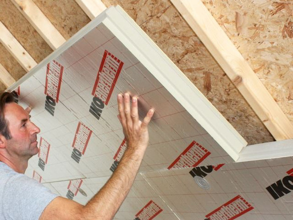 Insulation being placed under pitched roof