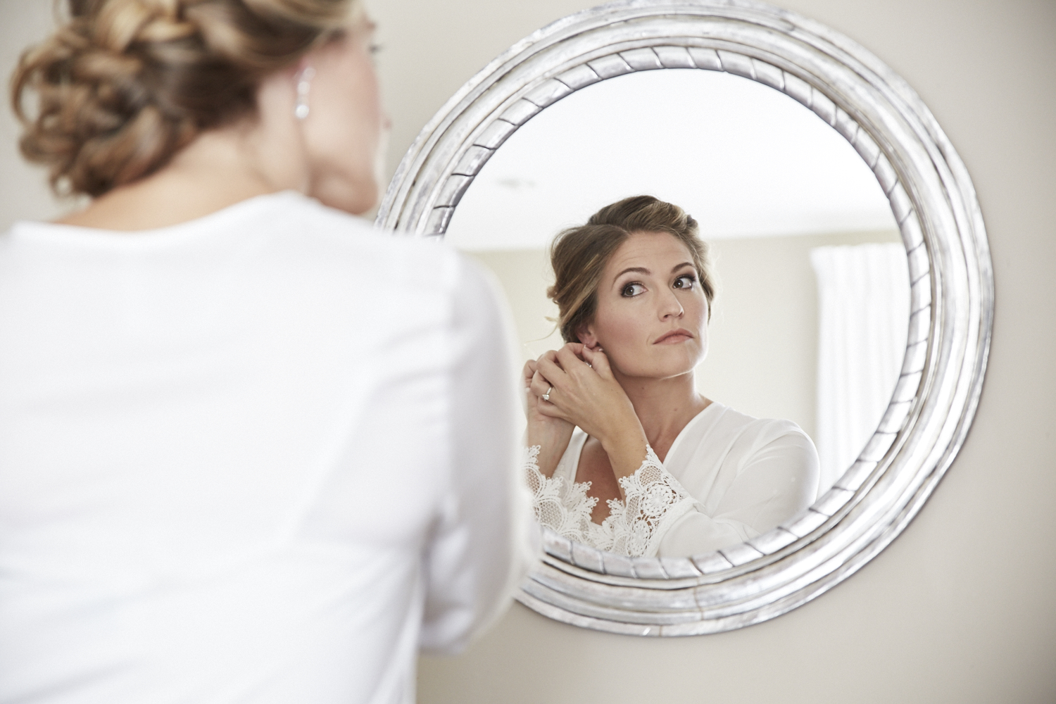 Bride looks in silver mirror
